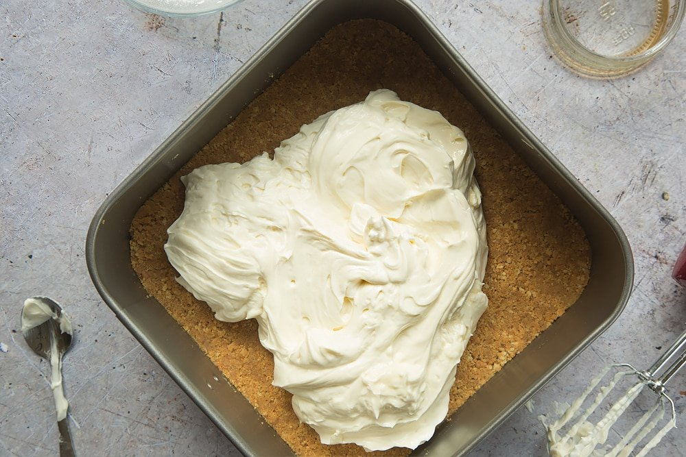 Overhead shot of cream cheese mixture on top of digestive biscuits crust in a square loose-bottomed straight-sided tin surrounded by a mixer, jar, and spoon