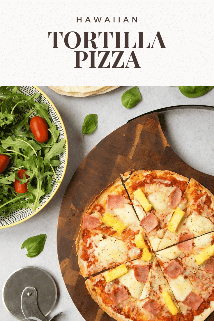 Overhead shot of an hawaiian tortilla pizza on a wooden board with a salad on the side. At the top of the image there's some text describing the image for Pinterest.