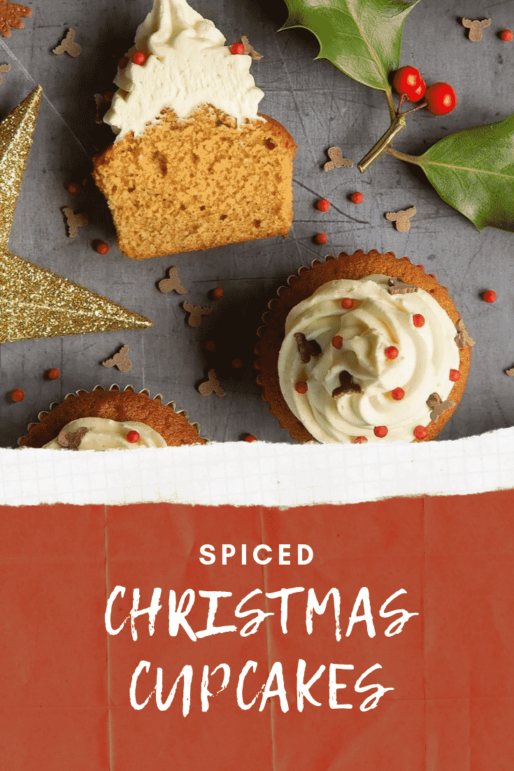 Overhead shot of the finished spiced Christmas cupcakes on a grey table decorated with festive sprinkles. At the bottom of the image there's some white text on a red background describing the image for Pinterest.