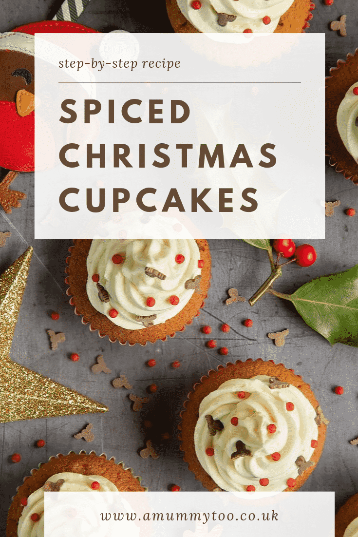 Overhead shot of the finished spiced Christmas cupcakes with marzipan frosting on a grey table decorated with festive ornimants. At the top of the image there's some brown text on a white background describing the image for Pinterest.