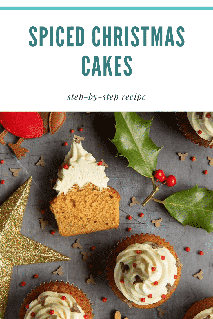 Overhead shot of the finished spiced Christmas cupcakes with marzipan frosting on a grey table. At the top of the image there's some teal text describing the image for Pinterest.