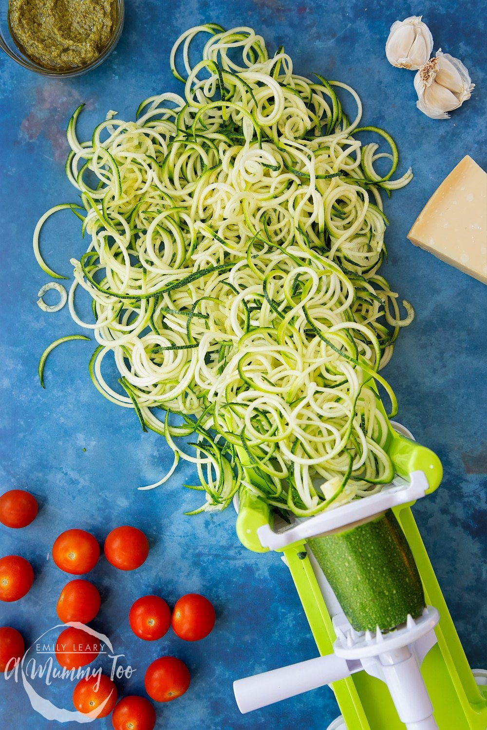 Spiralised courgette coming out of a spiraliser, surrounded by tomatoes, pesto, garlic and Parmesan