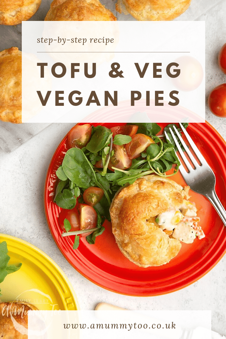 Overhead shot of a red plate with a vegan tofu pie cut open with a salad on the side. There's an additional yellow plate on the side doing the same and some additional pies on a marble chopping board at the top of the image.
