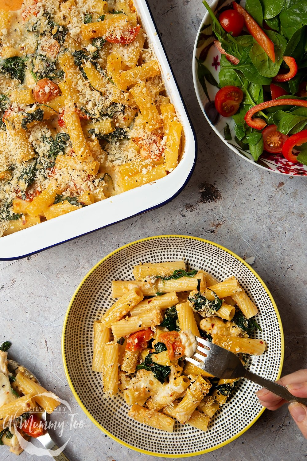 A fork going into the bowl of Cherry tomato, spinach and garlic mozzarella pasta bake. The bowl is sat alongside the pan with the remainder of the Cherry tomato, spinach and garlic mozzarella pasta bake alongside a side salad.