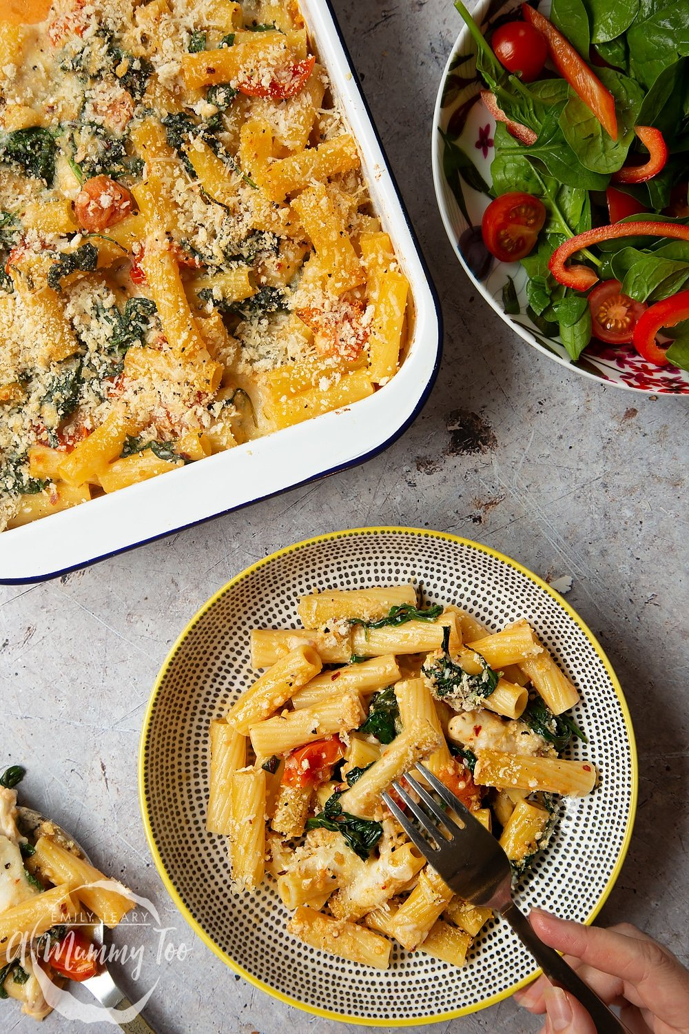 Overhead shot of a decorative bowl with a serving of Cherry tomato, spinach and garlic mozzarella pasta bake alongside the pan and a side salad.