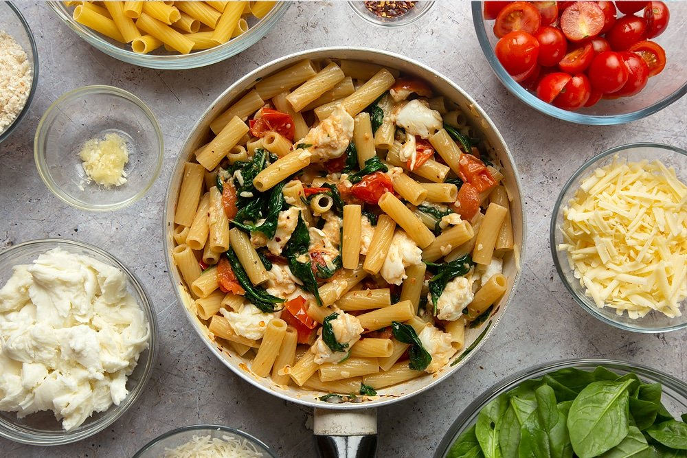 The cooked ingredients for Cherry tomato, spinach and garlic mozzarella pasta bake mixed together.