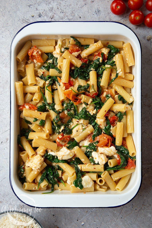 Cherry tomato, spinach and garlic mozzarella pasta bake in a roasting tin.