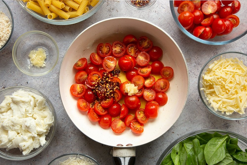 Some of the ingredients for the Cherry tomato, spinach and garlic mozzarella pasta bake being added to the pan.
