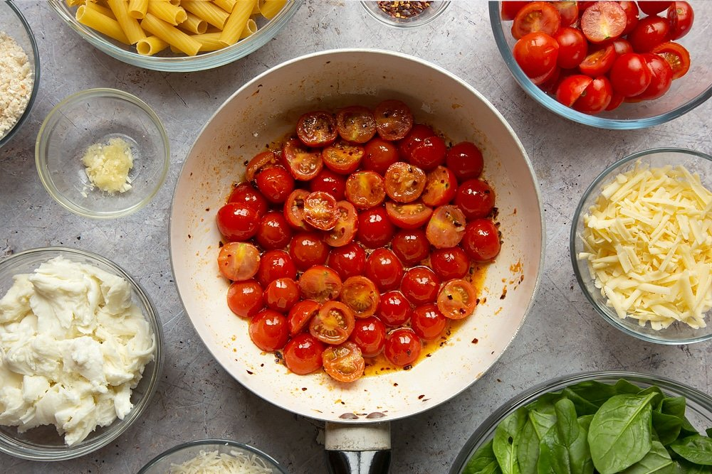 Chopped cherry tomatoes in the pan having been cooked. The shot is taken overhead and the pan is surrounded by ingredients required to make the Butter melting in a pan surrounded by different ingredients required to make Cherry tomato, spinach and garlic mozzarella pasta bake.