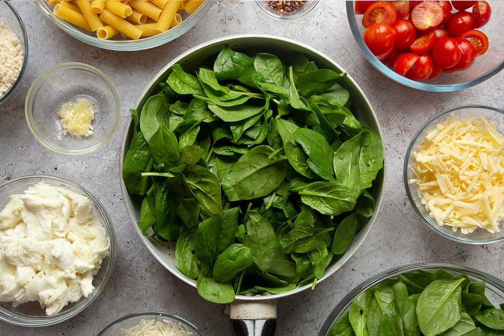 Overhead shot of spinach in a pan surrounded by ingredients required to make the Butter melting in a pan surrounded by different ingredients required to make Cherry tomato, spinach and garlic mozzarella pasta bake.