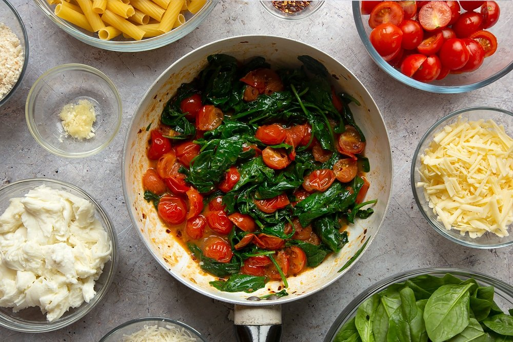 Spinach and tomatoes having been cooked in a pan. These are two of the ingredients required to make the Butter melting in a pan surrounded by different ingredients required to make Cherry tomato, spinach and garlic mozzarella pasta bake.