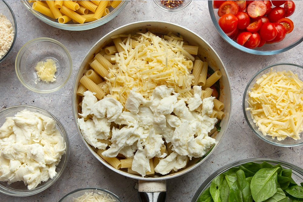 Cheeses being added to the pan of semi cooked pasta. Surrounded by additional ingredients required to make the Butter melting in a pan surrounded by different ingredients required to make Cherry tomato, spinach and garlic mozzarella pasta bake.