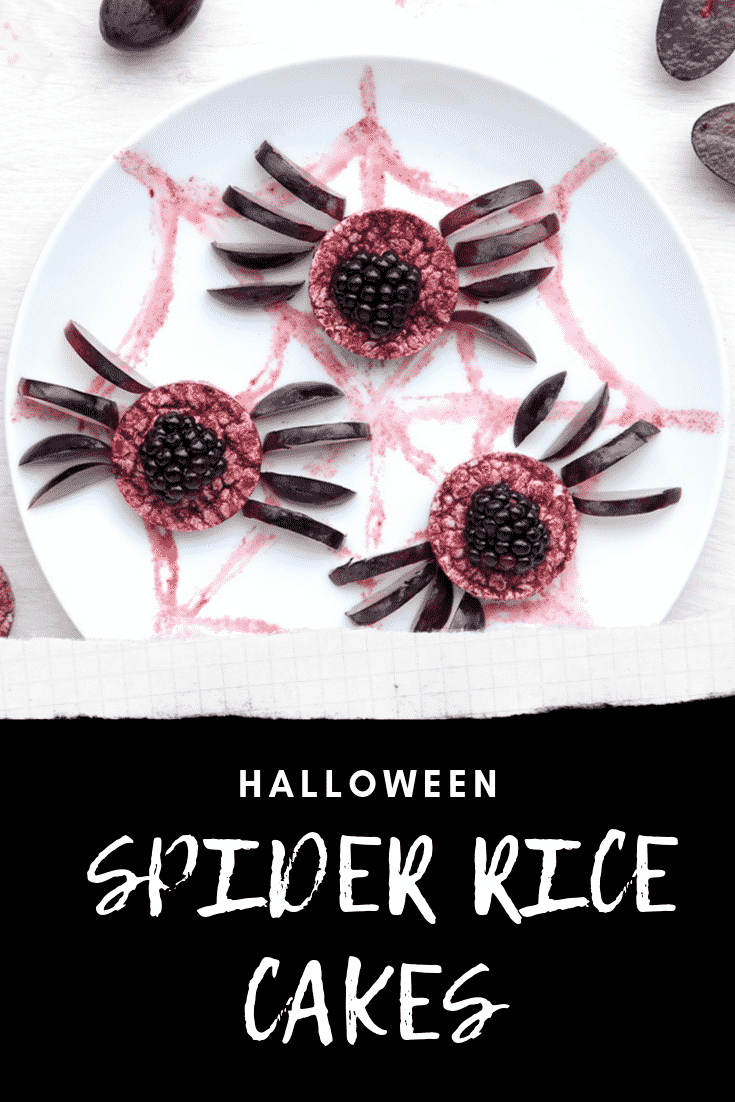 Halloween rice cakes, decorated with blackberries & grapes to look like spiders on a spider's web. Caption in white text on black reads: Halloween spider rice cakes.