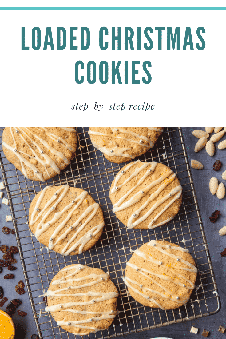 Six loaded Christmas cookies on a cooling rack on top of a dark grey counter top. There's some text at the top of the image describing the image for Pinterest.