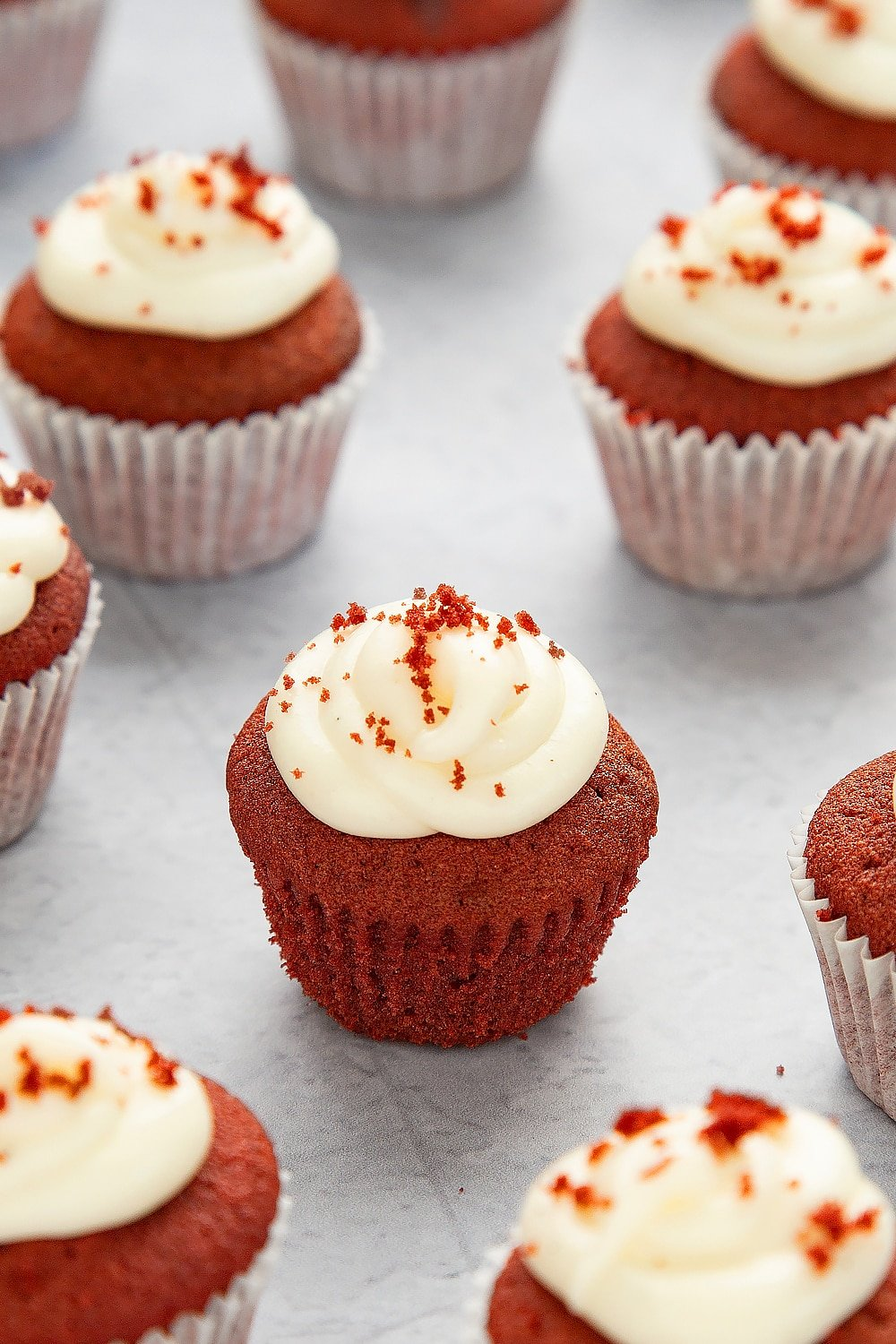 Mini red velvet cupcakes with cream cheese frosting unwrapped from it's case sat on a grey table top surrounded by additional cupcakes.
