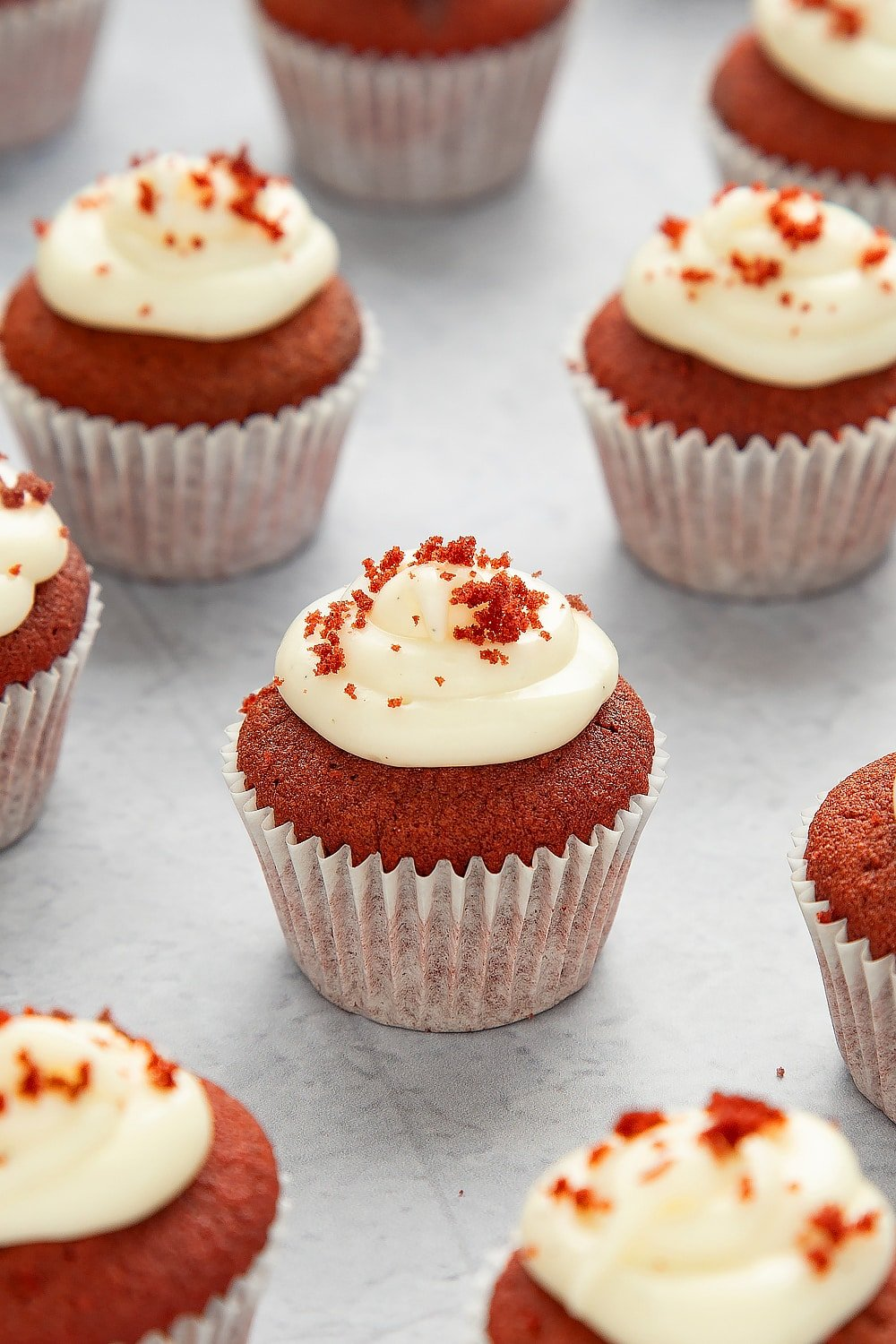Mini red velvet cupcakes with cream cheese frosting on a grey table top.
