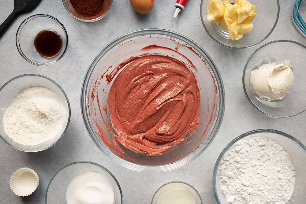 Mixing together some of the ingredients required to make the mini red velvet cupcakes with cream cheese frosting in a glass bowl.
