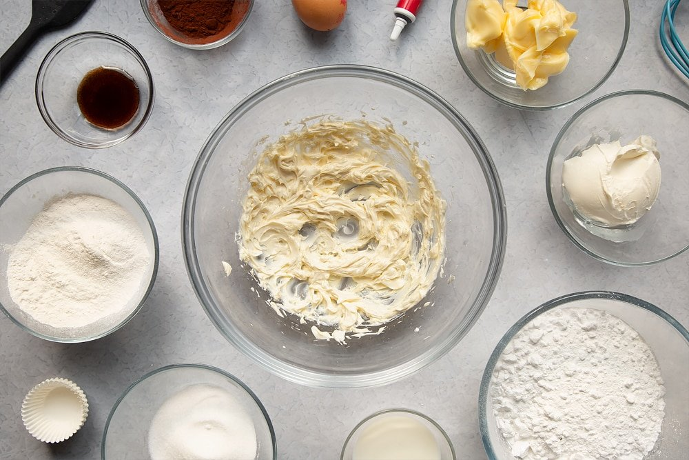 Overhead shot of a bowl of ingredients for the cream cheese frosting being mixed togethered surrounded by additional ingredients which are required for the recipe.