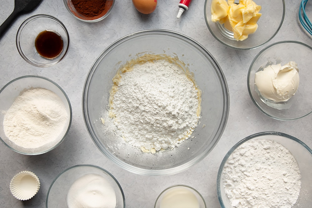 Adding icing sugar to the bowl of ingredients to make the cream cheese frosting.