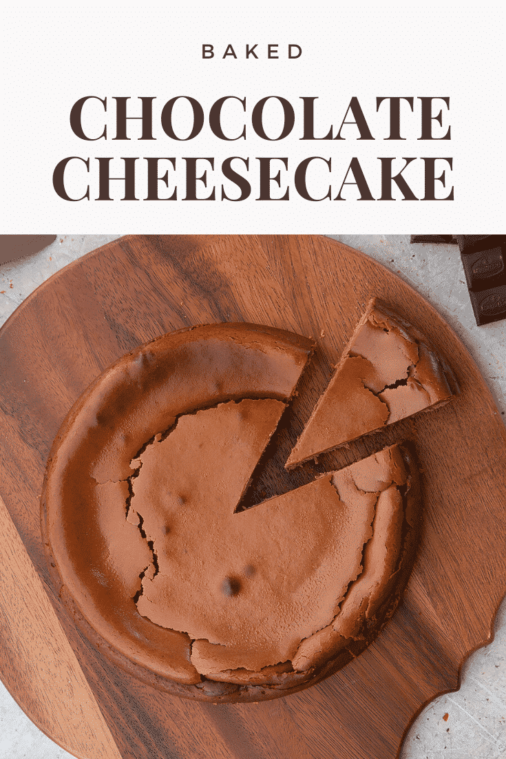 Close up overhead shot of the baked chocolate cheesecake with a slice cut out on a wooden board. At the top of the image there's some text describing the image for Pinterest.