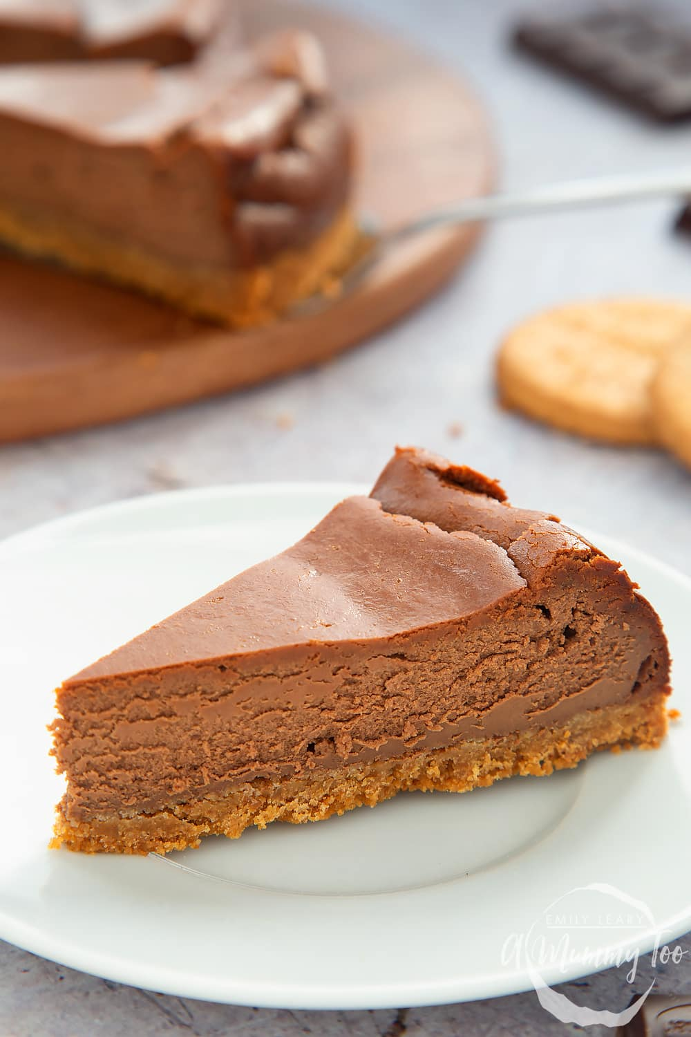 Close up of the side of the baked chocolate cheesecake on a white plate.