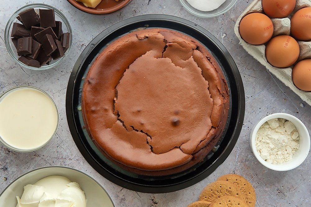 Overhead shot of the finished baked chocolate cheesecake surrounded by some of the ingredients which have been used in the recipe.