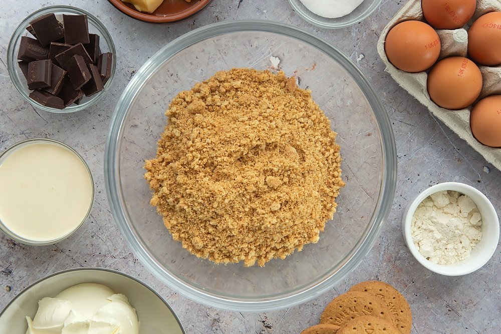 Overhead shot of the digestive biscuits required to make the baked chocolate cheese cake mashed up together inside a bowl surrounded by some of the additional ingredients required to make the baked chocolate cheesecake.