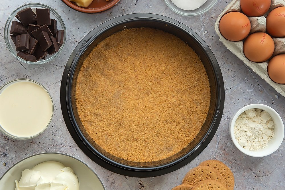 Overhead shot of the base of the cheesecake having been patted down until even and firm inside a tin and baked for five minutes. Some of the additional ingredients required for the baked chocolate cheesecake surround the tin.