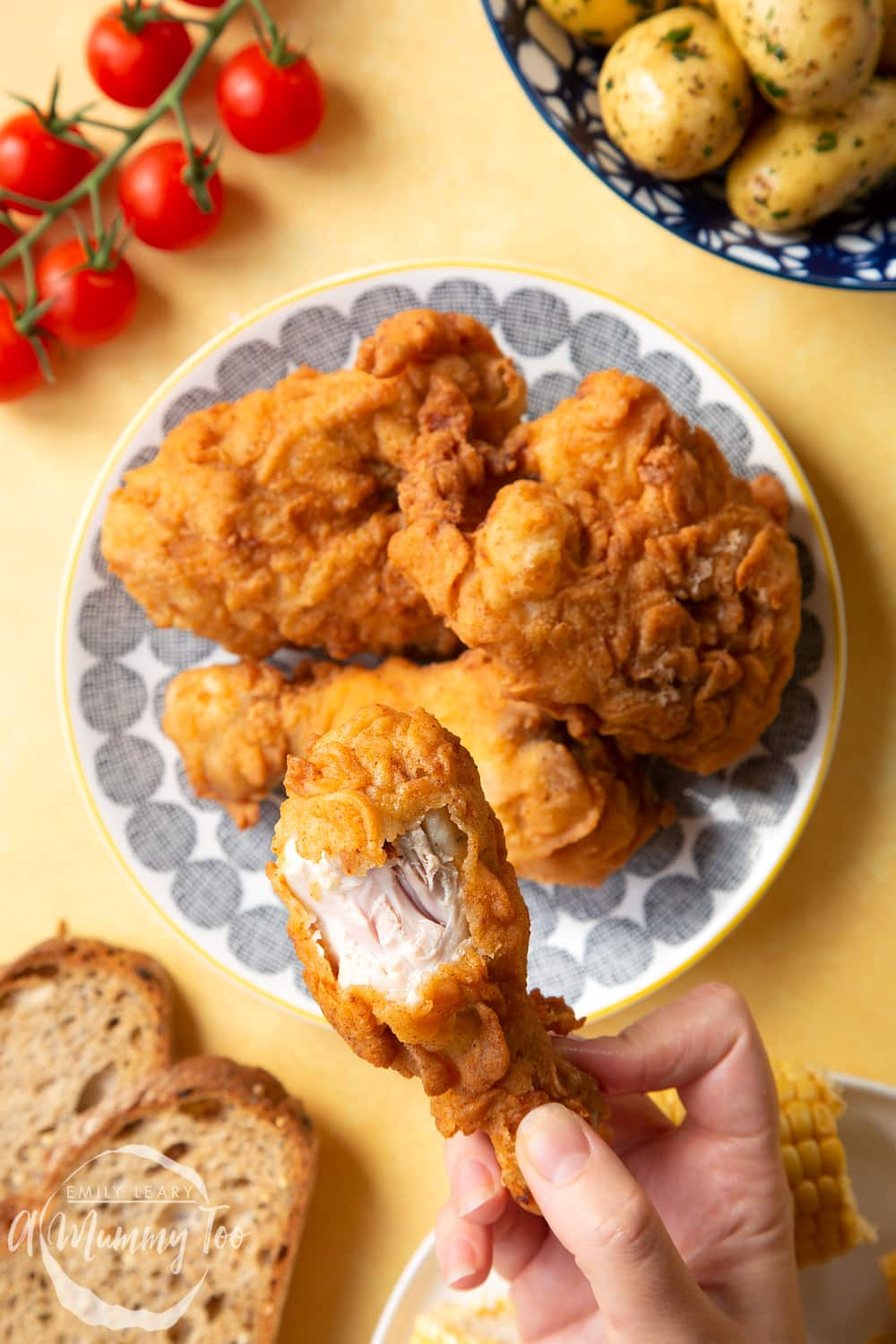 Gordon Ramsay's buttermilk fried chicken arranged on a plate, surrounded by tomatoes, potatoes, bread and corn on the cob. A hand holds a well-coated drumstick, with the juicy chicken showing underneath the seasoned coating.