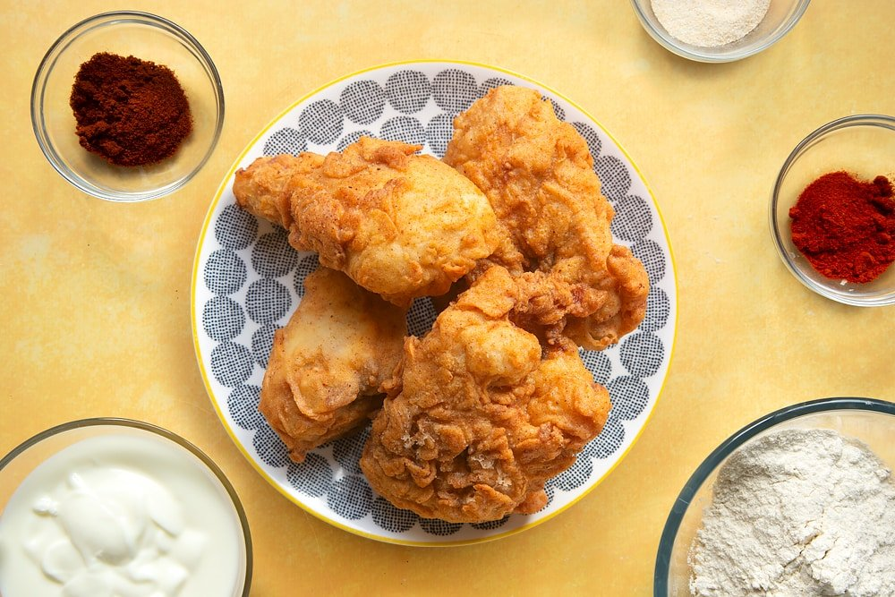 Freshly cooked buttermilk fried chicken on a patterned plate, surrounded by ingredients.
