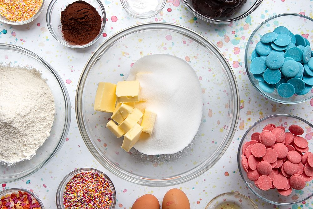 Sugar and cubed butter in a bowl. Ingredients to make a cake pop bouquet surround the bowl.