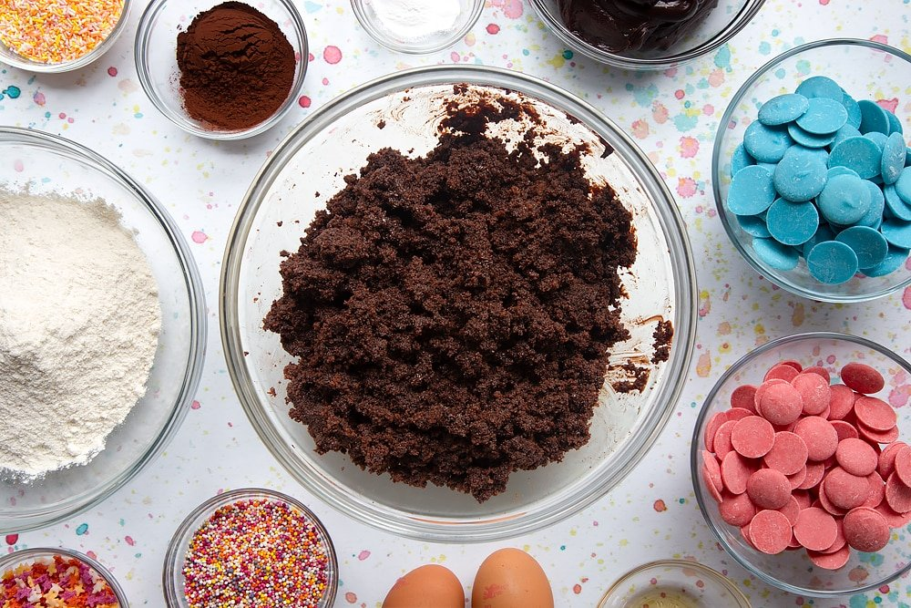 Chocolate cake crumbled in a bowl and mixed with chocolate frosting. Ingredients to make a cake pop bouquet surround the bowl.