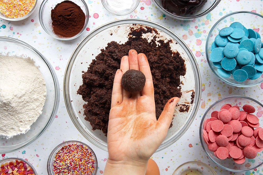 Chocolate cake crumbled in a bowl and mixed with chocolate frosting. A hand holds a ball of mixture. Ingredients to make a cake pop bouquet surround the bowl.