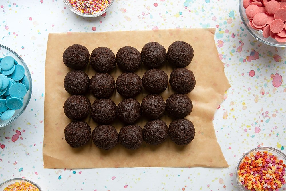 Rows of chocolate cake balls on baking paper. Ingredients to make a cake pop bouquet surround the paper.