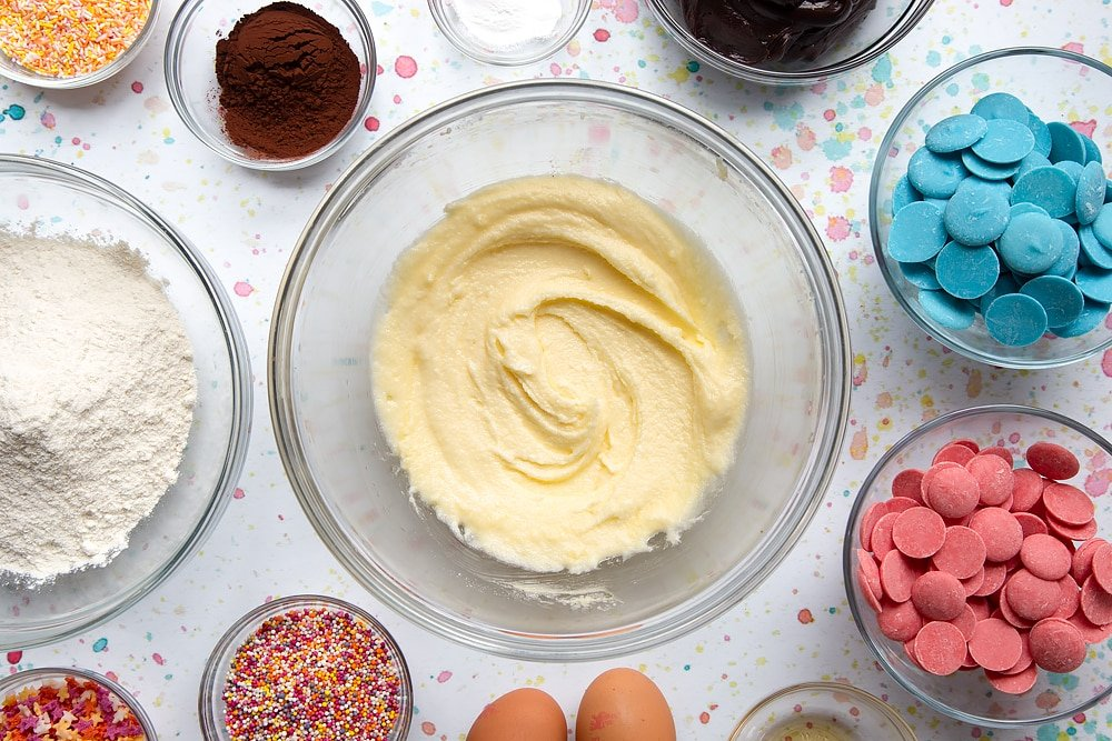 Sugar and butter creamed together in a bowl. Ingredients to make a cake pop bouquet surround the bowl.