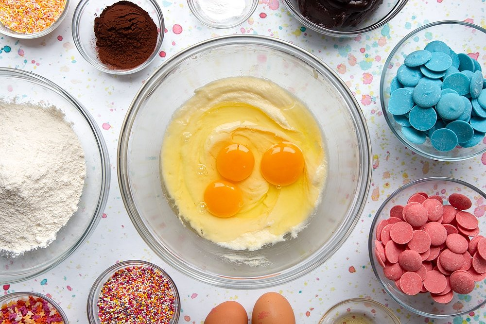 Sugar and butter creamed together in a bowl with eggs on top. Ingredients to make a cake pop bouquet surround the bowl.
