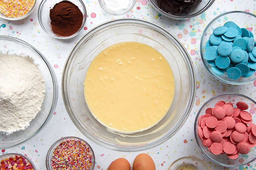 Sugar, butter and eggs creamed together in a bowl. Ingredients to make a cake pop bouquet surround the bowl.