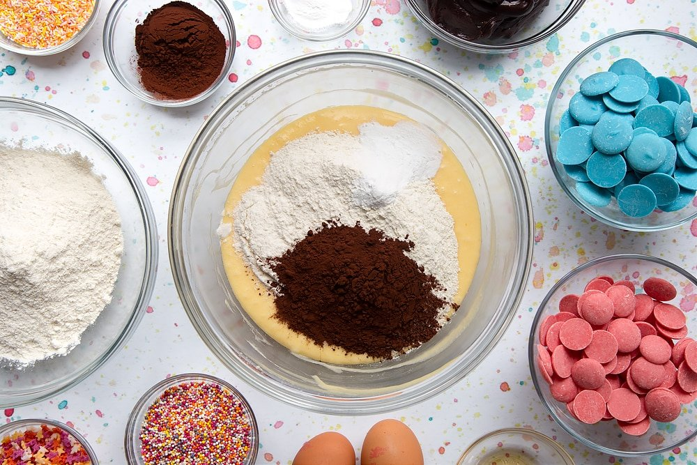 Sugar, butter and eggs creamed together in a bowl with flour, cocoa and baking powder on top. Ingredients to make a cake pop bouquet surround the bowl.