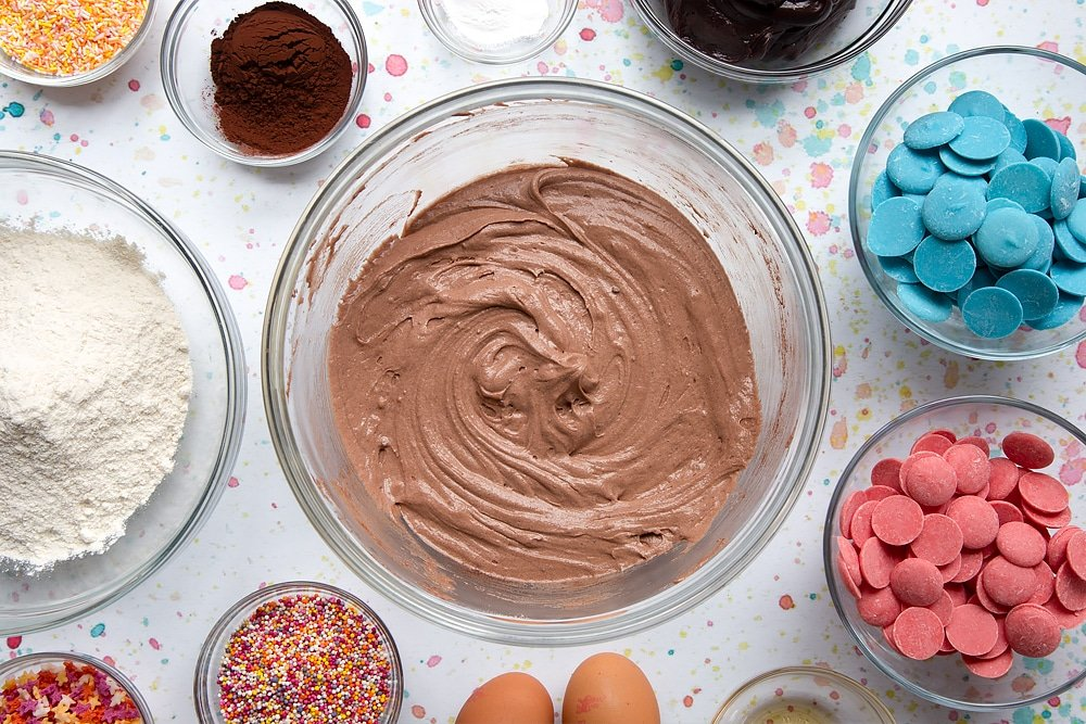 Chocolate cake batter in a bowl. Ingredients to make a cake pop bouquet surround the bowl.