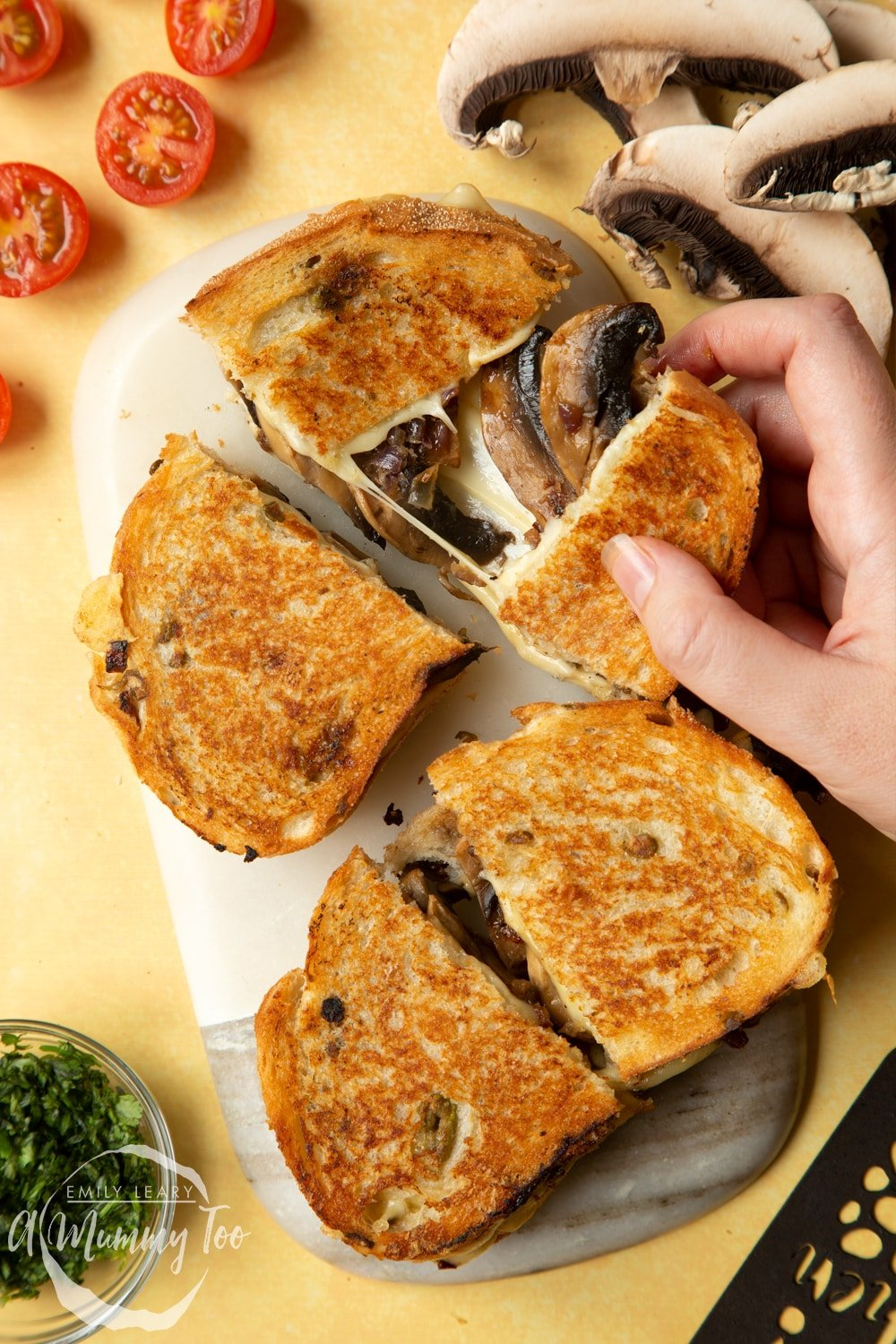Two Jarlsberg cheese and mushroom toasties are on a serving board, one is being pulled apart so the cheese and mushrooms stretch out between them.