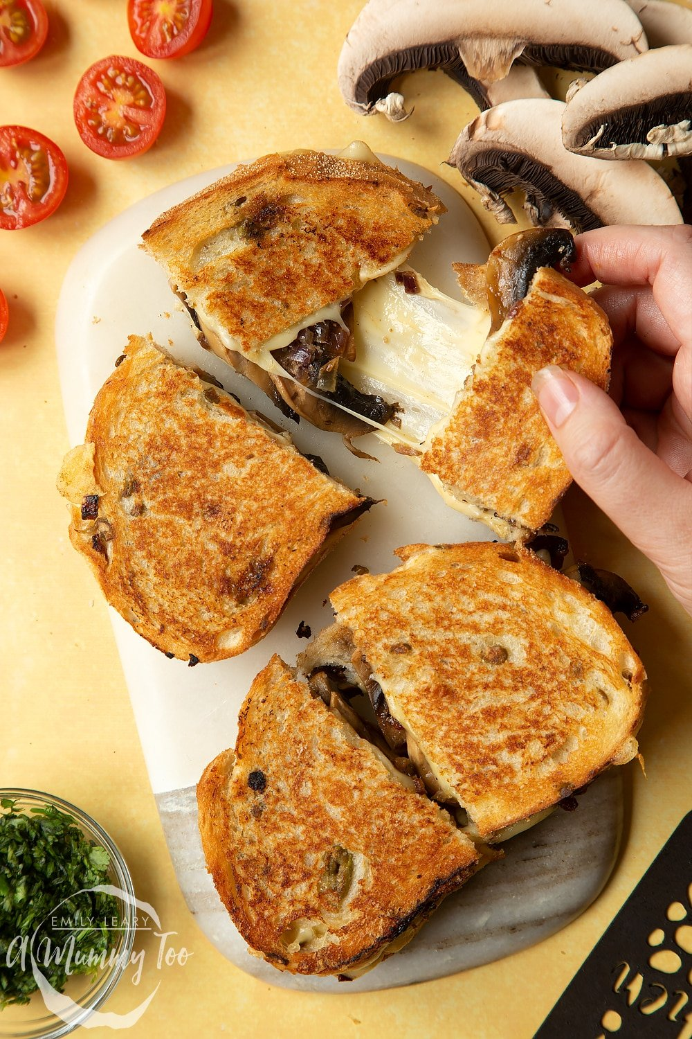 Two Jarlsberg cheese and mushroom toasties are on a serving board, one is being pulled apart so the cheese stretches out between them.