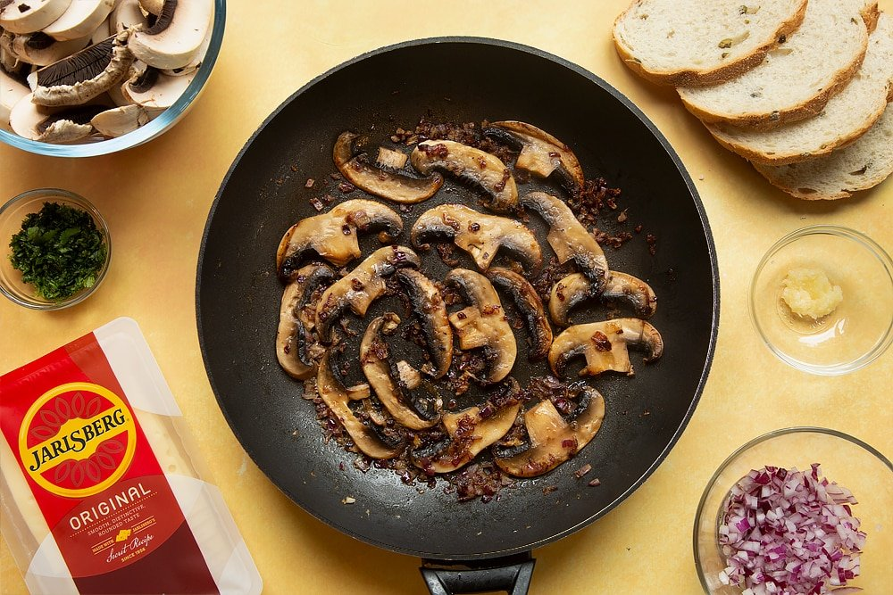 A frying pan with cooked garlic, onions, cayenne and black pepper in along with cooked mushrooms.