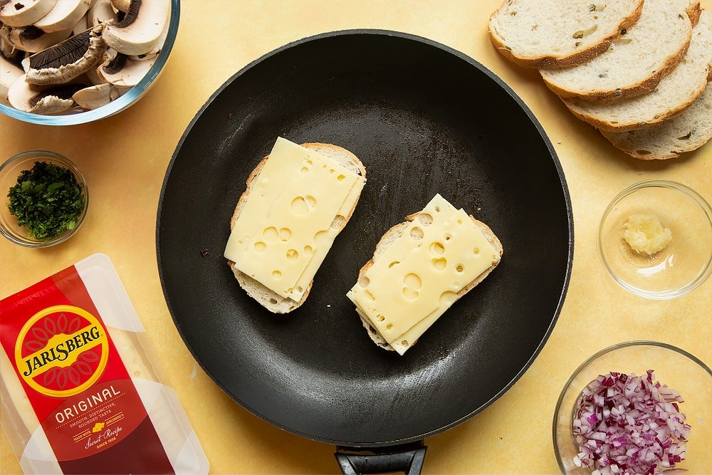 A frying pan with two slices of bread side by side and Jarlsberg cheese on top of both.