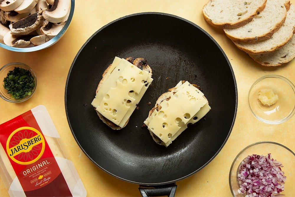 A frying pan with two slices of bread side by side and Jarlsberg® cheese on top, followed by cooked mushrooms, followed by more Jarlsberg cheese.