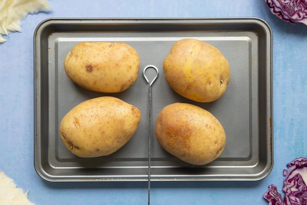 Four baking potatoes on a tray with a skewer. Ingredients to make jacket potato with homemade coleslaw surround the tray.
