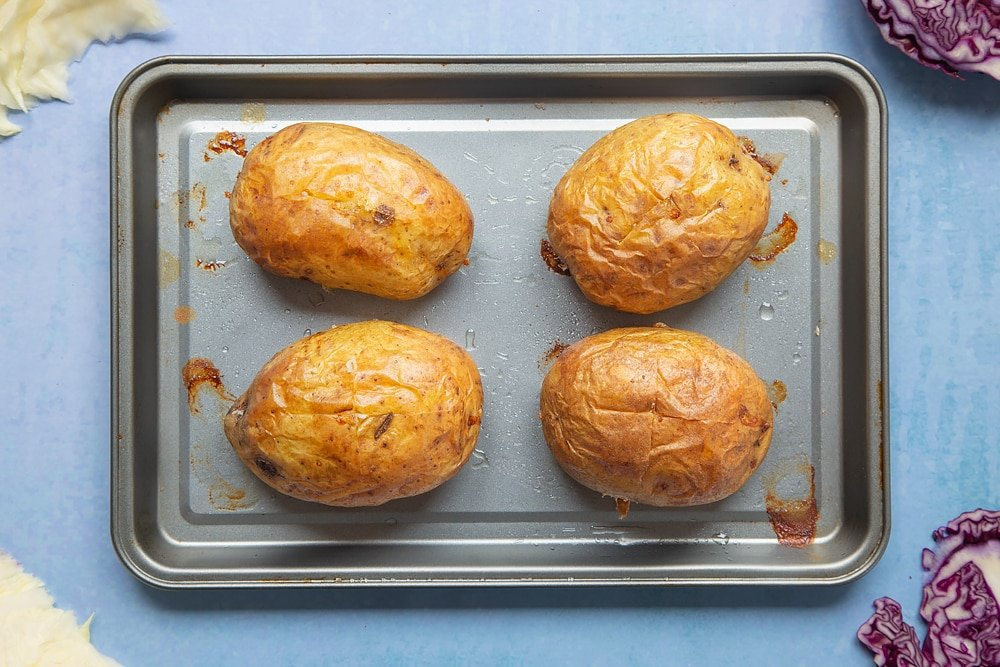 Four baked potatoes on a tray. Ingredients to make jacket potato with homemade coleslaw surround the tray.