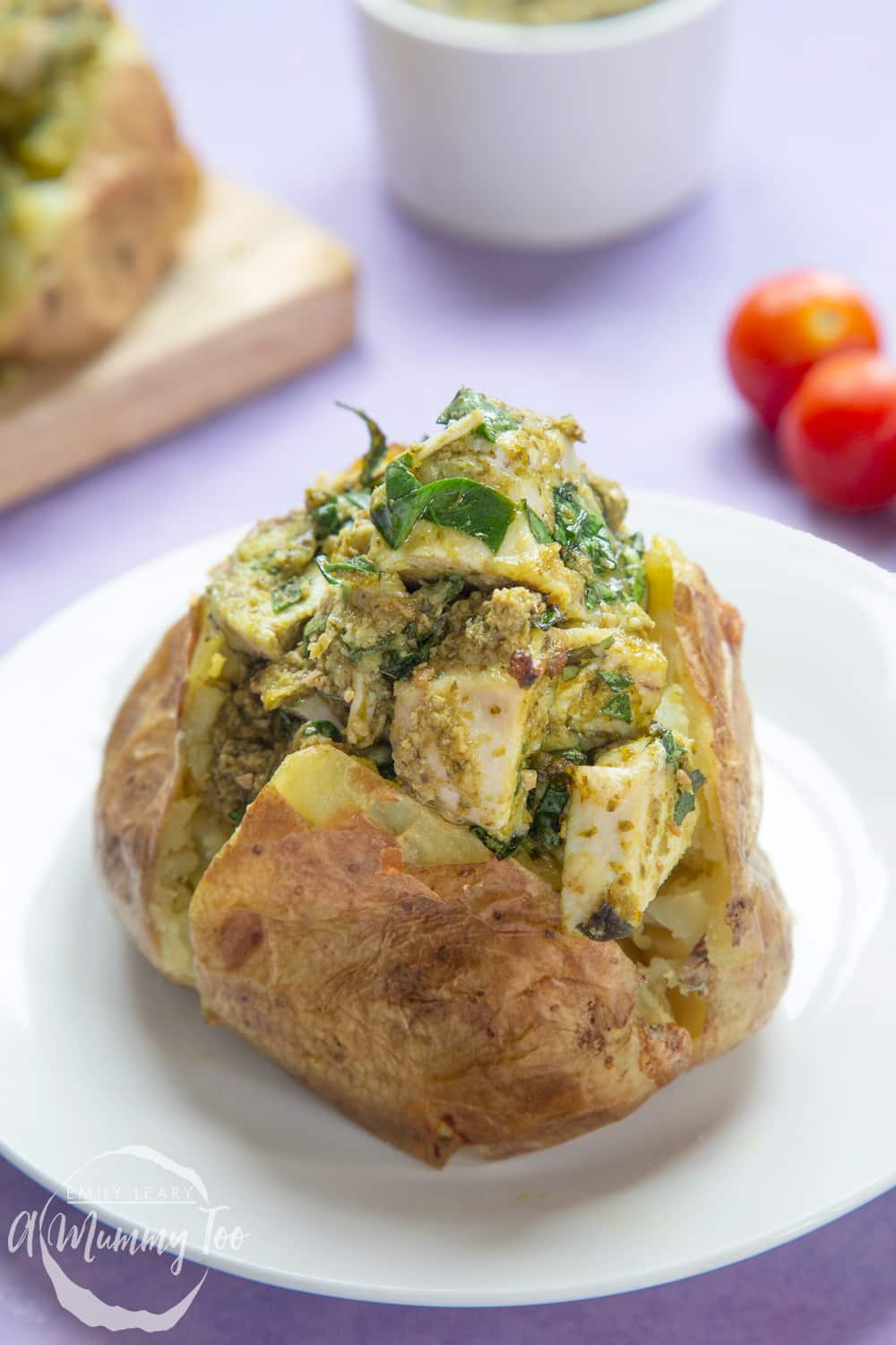 Jacket potato with cheesy pesto chicken on a white plate. The potato is piled high with a pesto, spinach cheese and chicken mix.