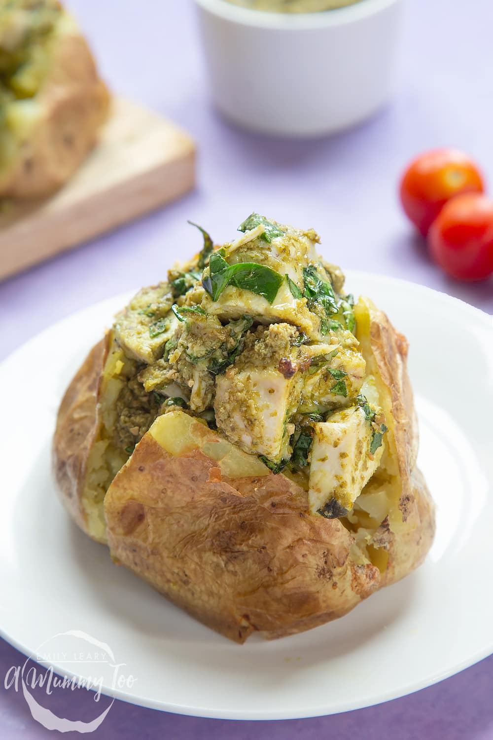 A jacket potato with cheesy pesto chicken on a white plate. The potato is piled high with a pesto, spinach cheese and chicken mix. More potatoes sit on a board in the background.