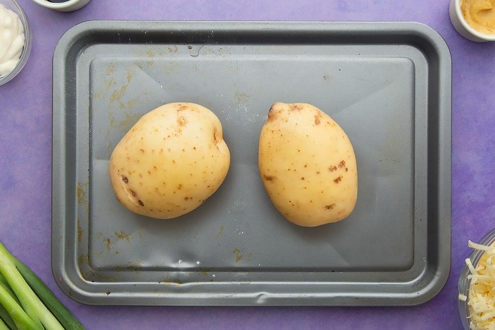 Raw baking potatoes on a baking tray. Ingredients to make jacket potato with cheesy pesto chicken surround the tray.