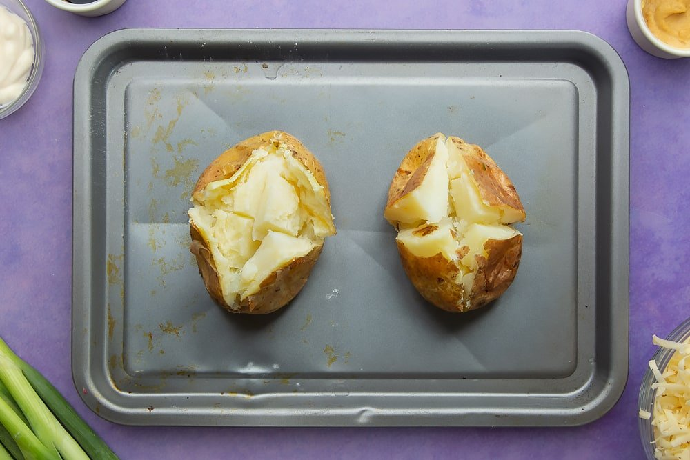 Baked potatoes cooked and cut open on a baking tray. Ingredients to make jacket potato with cheesy pesto chicken surround the tray.